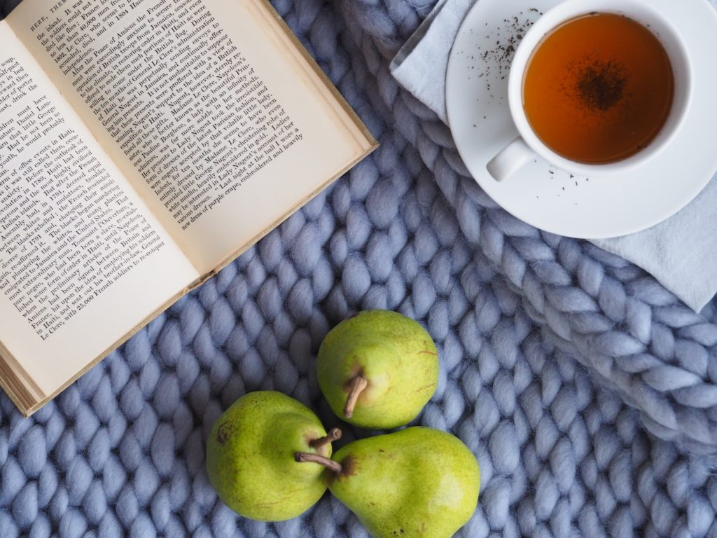 an open book, cup of tea, and three green pears set on a cornflower blue knitted blanket