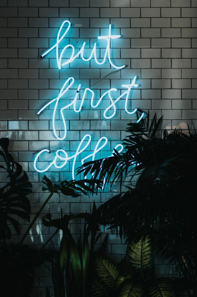 "A blue neon sign that reads ""but first, coffee"" against a white brick wall with palm trees"