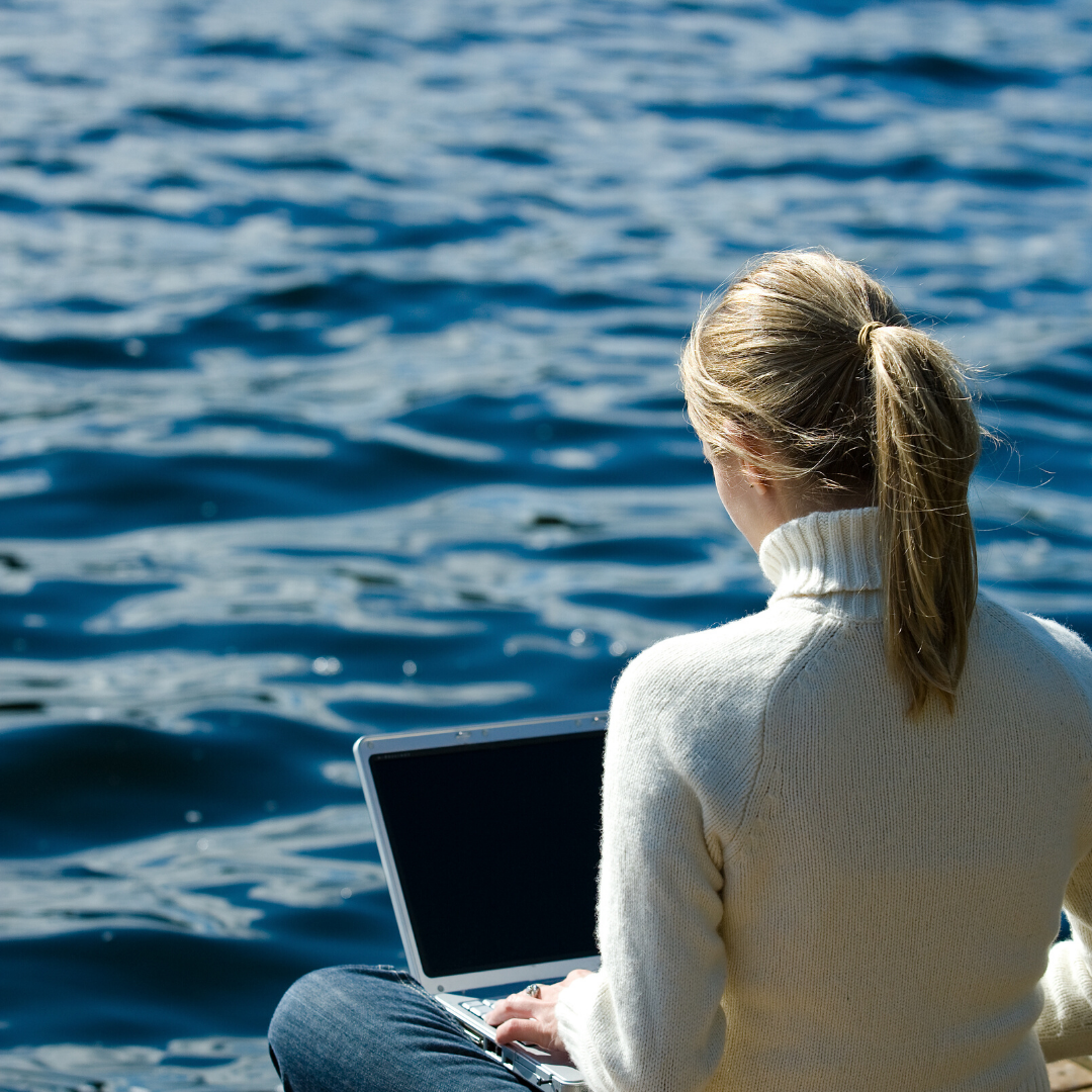 woman attending a virtual coaching session by a lake