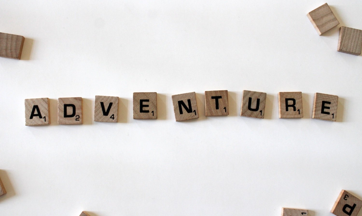 scrabble tiles spelling out the word adventure