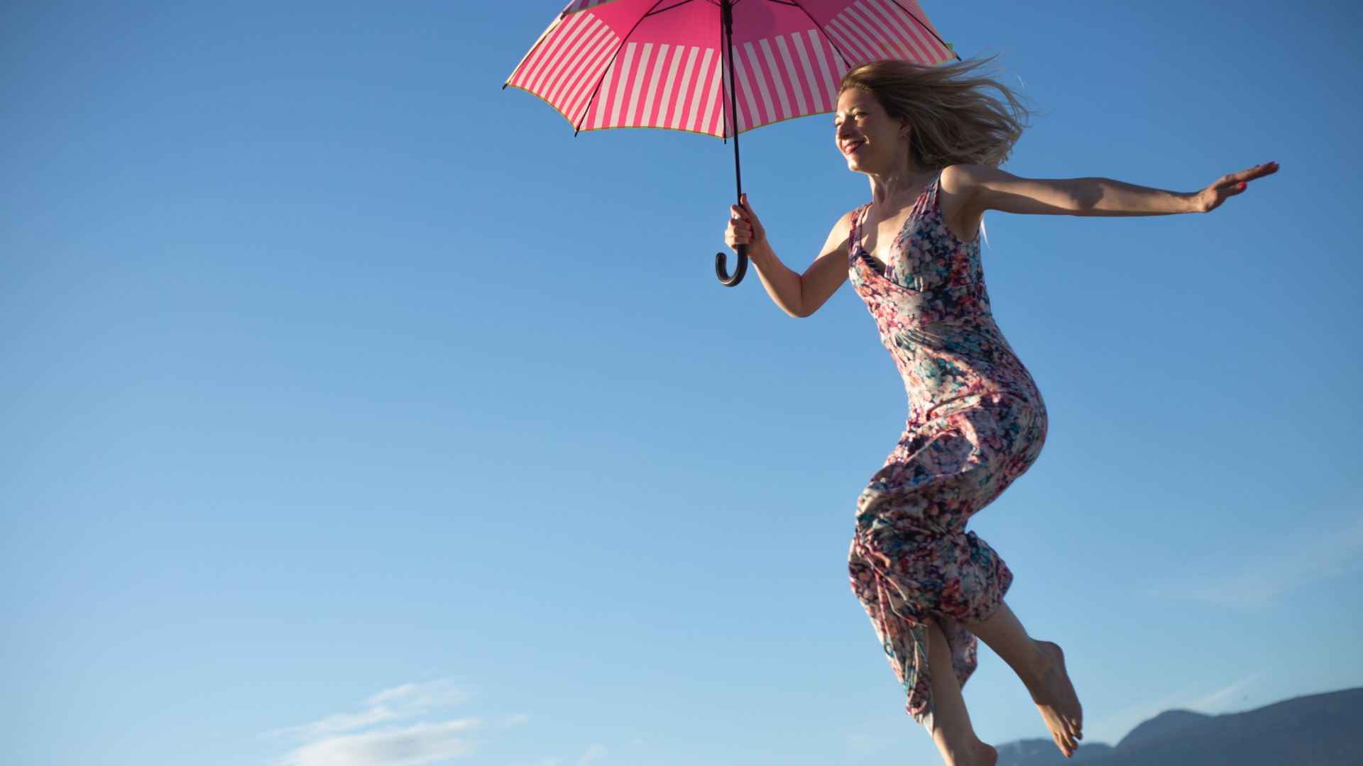 woman up in the air holding a pink umbrella