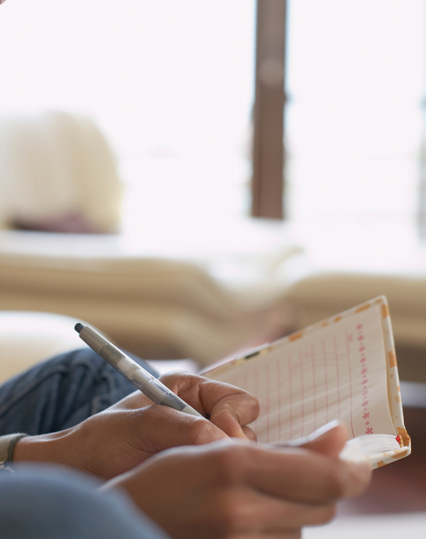 a person taking notes in their journal during a virtual coaching session
